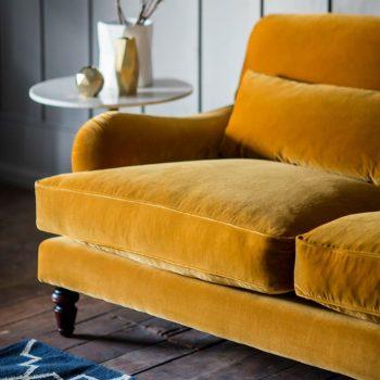 photo de canapé jaune en velours avec tapis bleu